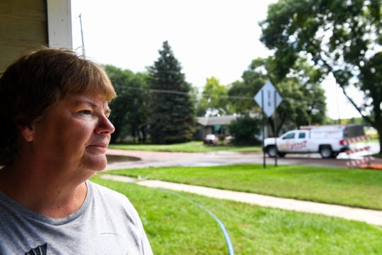 Dawn Foster, resident of Madison, SD, looks out at her neighborhood while taking a break from cleanup after her basement was flooded to the ceiling on Thursday, September 12. She said the room was filled in 20 minutes.