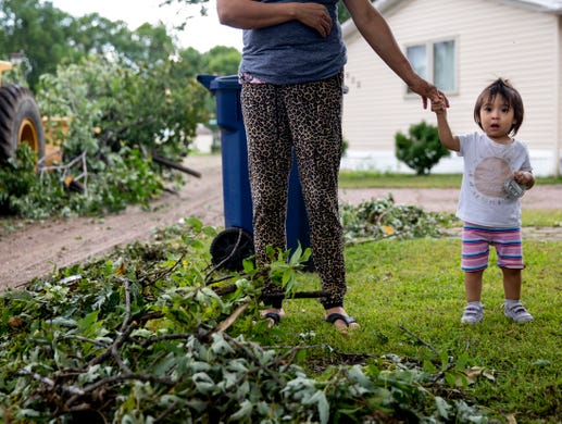 Sandra Hernandez holds her daughter Alexa's hand as she watches crews clean up trees in Johnson Estates on Thursday, Sept. 12, 2019. Three tornadoes touched down leaving a path of destruction in Sioux Falls on Tuesday, Sept. 10, 2019.
