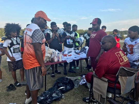 Coach Tyrone Williams (left) and Coach James Neal (seated) give out Tallahassee Warriors football uniforms to the team on Wednesday, Sept. 11, 2019.