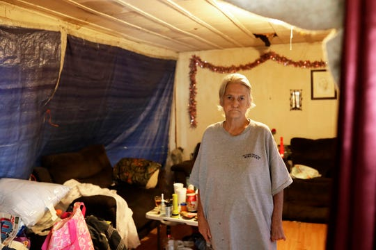 Beverly Freeland, a resident of Altha, Fla., stands in what doubles as her living room and bedroom ever since Hurricane Michael tore through her small community in Oct. 2018. The blue tarp separates her living quarters from the leaks and mess in the rest of her home.