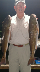 Mark Hillis with a pair of fine redfish he caught fishing with Capt Junior Dice.