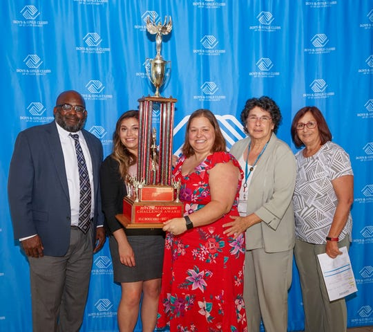 The St. Lucie County Commission's Library Division took the top spot in the book-themed 37th annual Chili Cook-Off by being the top in three categories of chili, fundraising and showmanship. Will Armstead, left, CEO of the St. Lucie County Boys & Girls Clubs and County Commissioner Linda Bartz, right, present the trophy to the Library Division's Amanda Carranza, Jesse Wilson and Susan Jacob.