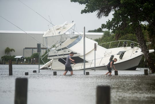Noah Sweet (left), 13, and Landon Sweet, 11, make their way past a tipped-over boat at Sandsprit Park in Martin County on Tuesday, Sept. 3, 2019, while area residents keep an eye on Hurricane Dorian's track. A pier at the park was damaged by Hurricane Dorian.