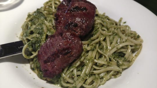Tallarin verde con bisteck, a tender skirt steak served on a bed of green pasta with a pesto and spinach sauce bursts with flavor at Inti International Restaurant.