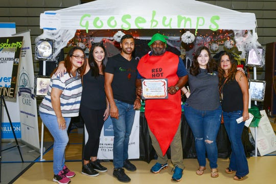 St. Lucie County Boys & Girls Clubs CEO  Will Armstead, center, awards the combined team of Tradition Family Chiropractic and Tradition Family Dental with the first-place Jim Lamb Memorial Chili Competition Award on July 13,  2019, at the Havert Fenn Center in Fort Pierce.