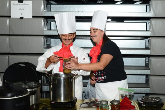 Fifth-grade student Gabby Gerheart, left, of Renaissance Charter School of St. Lucie West, and Christina Coburn mix their batch of chili to be used at the 37th annual Chili Cook-Off at the Fenn Center in Fort Pierce.