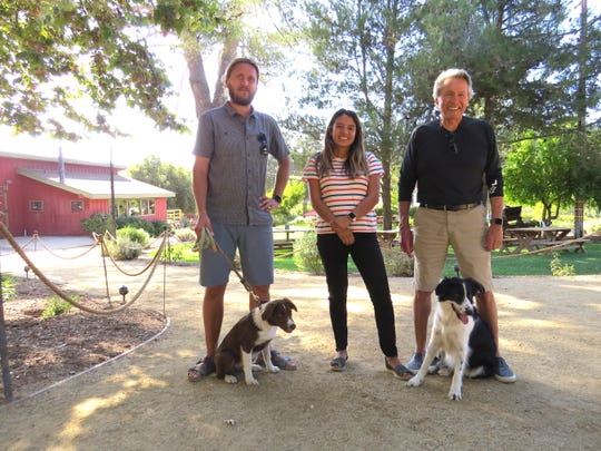 Old Creek Ranch Winery owner Andrew Holguin, right, poses with daughter Marie Holguin van Leeuwen, son-in-law Frans van Leeuwen and winery dogs  Ollie, left, and Vlinder. The winery's 1980s-era tasting room is seen in the background.