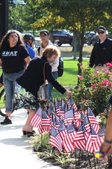 People who attended a ceremony to remember the attacks of September 11, 2001, at Rowan College of South Jersey in Vineland, placed flags around the campus fountain in honor of the victims.