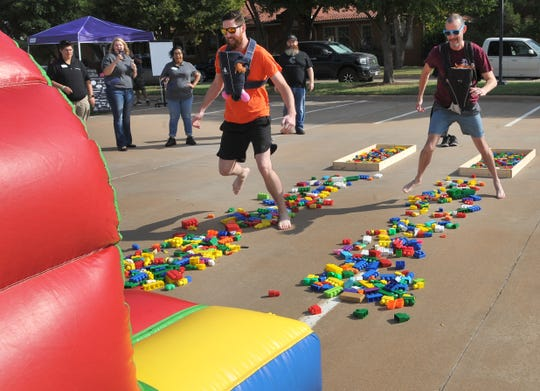 Wichita Falls public information officers Ben Remmert, left, and Eric Crosslin participate in Child Care Partners Playground Warriors obstacle course during the Texoma Gives annual fundraising event held in the parking lot of the MPEC Thursday morning.