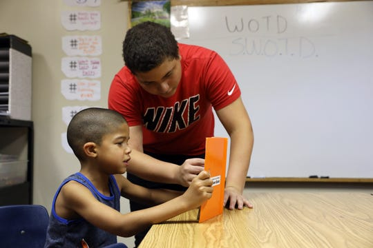 Koby Johnson reads with Jayceon Campbell, 6, at the Zanesville Civic League Civic Center recently.