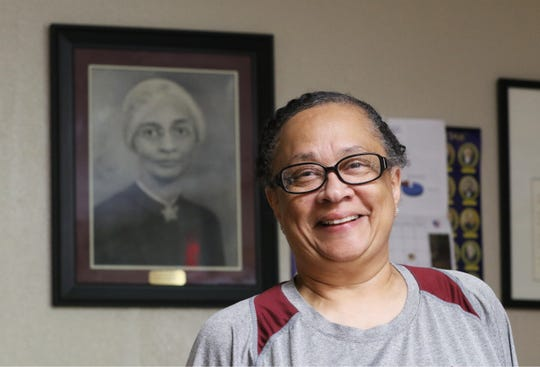 Lisa Rooks is the executive director of the Zanesville Civic League. Behind her is a portrait of Civic League Community Center founder Estalla Barnette.