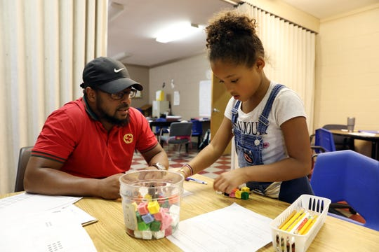 Adonis Brooks, assistant director of the Zanesville Civic League Civic Center, works on math problems with Samantha Norris, 8, during the Civic Center's after school program.