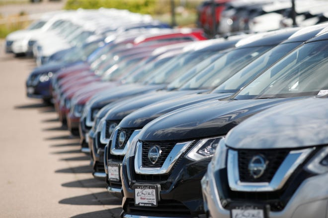 In this Sunday, Aug. 25, 2019, photograph, a long line of unsold Rogue sports-utility vehicles sit at a Nissan dealership in Highlands Ranch, Colo.