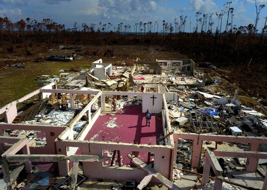 """Pastor Jeremiah Saunders poses for a photo among the ruins of his church that was destroyed by Hurricane Dorian, in High Rock, Grand Bahama, Bahamas, Wednesday Sept. 11, 2019. Jeremiah says """"I spoke to the water: 'Peace, be still.' It never listened,"""" Saunders said with a wide smile and then grew serious as he focused on the task that tens of thousands of Bahamians now face on two islands devastated by the Category 5 storm: the clean-up. (AP Photo / Ramon Espinosa) ORG XMIT: XRE106"""