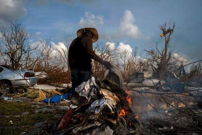 Mary Glinton burns clothes damaged by Hurricane Dorian in Mclean's Town, Grand Bahama, Bahamas, Wednesday Sept. 11, 2019. She created three piles of clothes stiffened by mud and water and set them on fire. A white lace curtain, a bright pink wind breaker and an old pair of black pants would soon go up in flames. She most lamented that all her church clothes were ruined. (AP Photo / Ramon Espinosa) ORG XMIT: XRE115