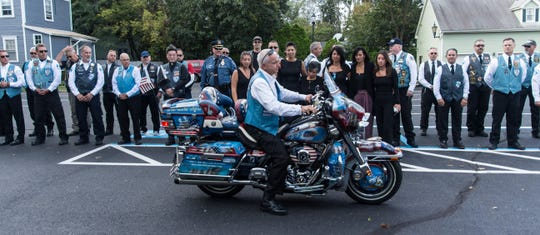 James Wishbow rides Al De Rosa's signature motorcycle. Mourners gather for Millstone resident Al DeRosa's funeral. He was the oldest member of the Blue Knights Law Enforcement Motorcycle Club as well as a retired NYPD officer and Air Force veteran. Friday, September 13th, 2019, in Freehold, New Jersey. (Contributor: EvaJo Alvarez)