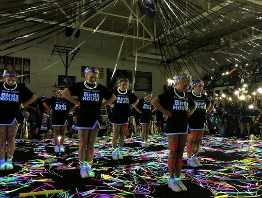Abilene High School cheerleaders finish a routine standing in a sea of glow sticks in Eagle Gymnasium Friday morning during the Crosstown Showdown pep rally.