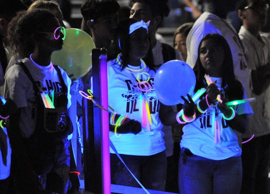 """The Cooper High School gym was awash in neon colors from black lights and glowing bracelets, necklaces, sticks and other items for the """"White Out"""" pep rally Friday."""
