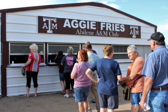 The line forms for Aggies Fries late Wednesday afternoon at the West Texas Fair & Rodeo. Volunteers promise quick service; it takes about 3 minutes for a basket of cut potatoes to become fries.