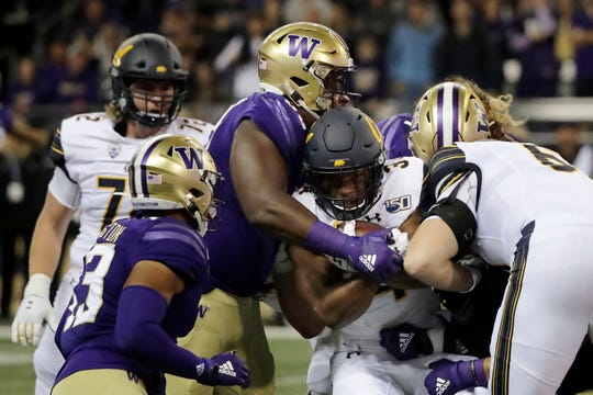 California running back Christopher Brown Jr., second from right, is tackled as he carries the ball against Washington during the first half Saturday, Sept. 7, 2019, in Seattle.