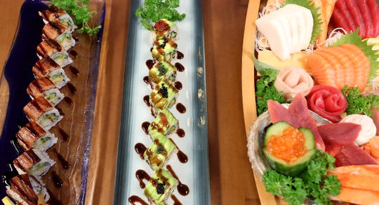 Colorful and intricate entrees, left to right, Dragon Roll, Caterpillar Roll and Sashimi in a wooden ship await tasting at Mori Sushi & Bento in Poulsbo on Thursday. The restaurant is the 19th for its owner, Morimoto Kim.