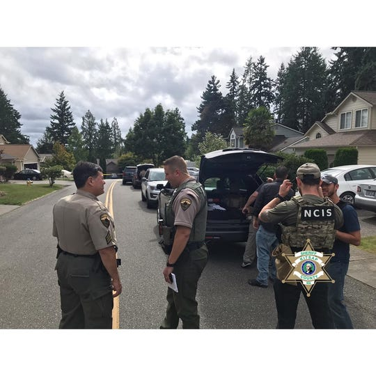 Officers gather Friday near the scene on Peony Place where a man had discharged a firearm. Family members told officers there may be explosive devices in the residence.