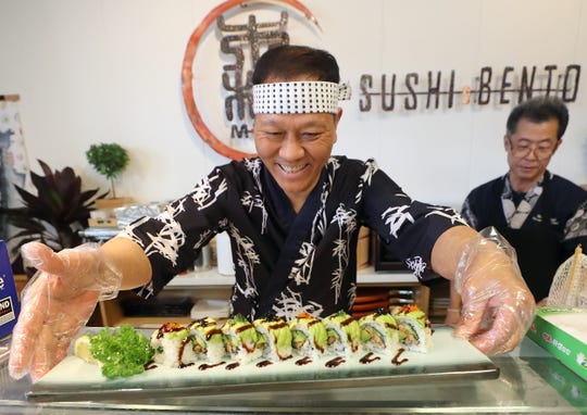 Chef Morimoto Kim places a Caterpillar Roll (grilled eel, avocado, cucumber and rice) on the counter at his Mori Sushi & Bento restaurant in Poulsbo, which opened this summer.