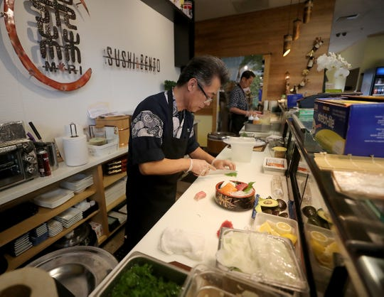 Sushi Chef Kenji Miyagi slices an avocado for a sashimi bowl at Mori Sushi & Bento in Poulsbo on Thursday.