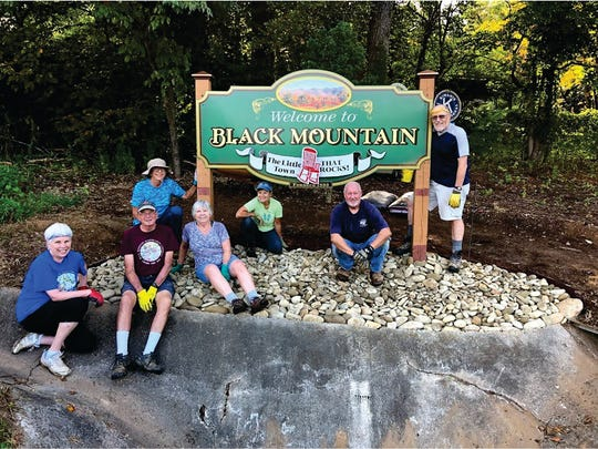 Black Mountain Beautification Committee members, from left to right, Kate Ramsey, Carl and Pat Reichenbach, Kathy Brown, Tracy Munn, Ron Wester and Peter Mudgetake, take a break from working on the welcome sign along N.C. 9.