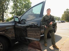 Black Mountain police officer Joseph Moore holds his department-issued Bushmaster AR-15 rifle. Moore was given a check by Chonzie McMahan to purchase new rifles for the department on Aug. 6, hours after the agency apprehended a suspect wanted in connection with a series of incidents.