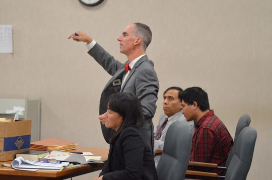 Attorney Brian Dodge speaks in Vermont Superior Court in Burlington on Friday, Sept. 13, 2019, about a judge's decision to hold his client, Aita Gurung, right, without bail.