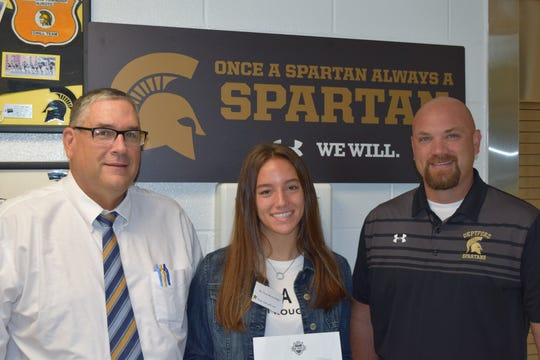 Deptford senior Angelina Schilling, center, won a national honor from the NFL on Friday. Spartans coach Al Orio, left, and Deptford principal Jeff Lebb are pictured with the kicker.