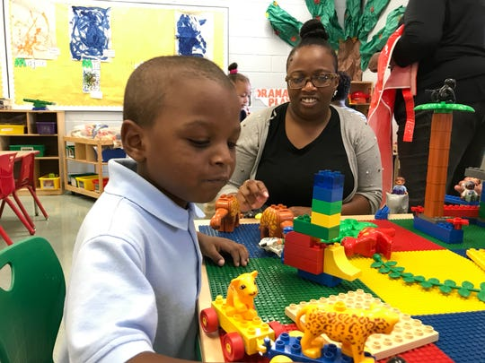 "Nykeem Douglas takes a lion and a leopard ""to the park"" while his teacher, Tyniesha Sturgis, watches in a pre-K class at RT Cream School in Camden."