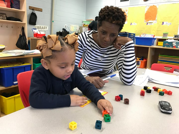 J'shya Andrews, 3, counts toy building blocks while her teacher, Zenetta Bronson, watches. Bronson is a teacher at R.T. Cream, which closed as a family school in June and reopened as an early childhood development center earlier this month.