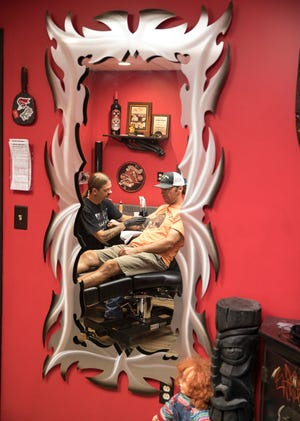 Danny Derreberry finishes a tattoo for Jamie Sharp, owner of River's Bend Bicycle Shop on Friday, Sept. 13, 2019, in his Wicked Sensations shop in Chillicothe.