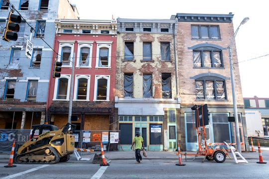 A construction worker walks along a stretch of Vine Street that's undergoing major redevelopment in Over-the-Rhine. New businesses have opened and incomes have increased in the past decade, but some former residents say they no longer can afford to live there.