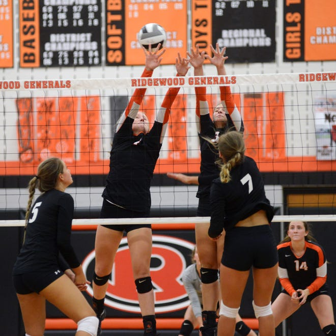 Hannah Maust, left, and Madisyn Colvin go up for a block for Ridgewood against Hiland last season. They are two of six returning players for the Generals.