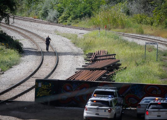 Members of the Des Moines Police Department work an area along the railroad tracks south of Grand Ave. on Friday, Sept. 13, 2019, in Des Moines after receiving a call about a shooting in the area.