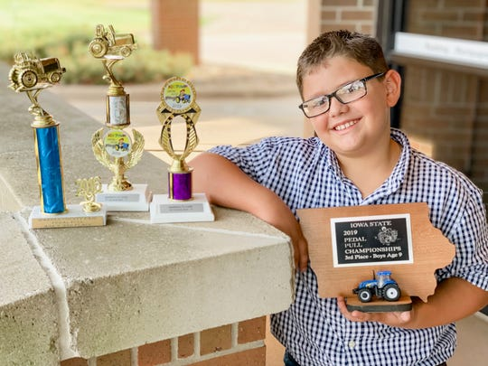Nine-year-old Ashton Binder poses with several trophies he has won in tractor pedal pull competitions.