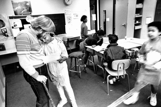 Kim Hetrick, a fourth-grade teacher at Friends School in Detroit, hugs a student at the school in 1987.
