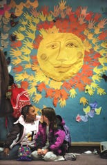 At the Friends School of Detroit Whitney Fant left, and Lena Kepler talk after school in front a a bulletin board that lists the hopes and dreams of the school's students in October, 2002.