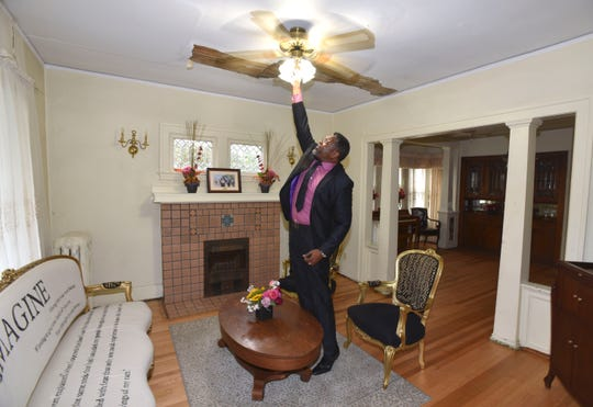 Daniel Baxter turns on the lights in the living room of the historic Ossian Sweet House in Detroit