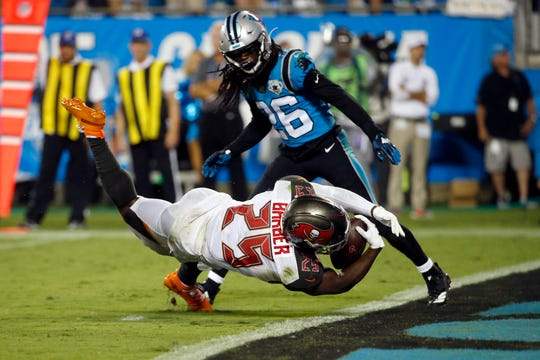 Tampa Bay Buccaneers running back Peyton Barber (25) scores while Carolina Panthers cornerback Donte Jackson (26) looks on during the second half on Thursday.