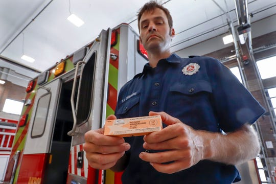 In this Sept. 11, 2019, photo, Akron fire medic Paul Drouhard shows a box containing naloxone that is carried in all the department's emergency vehicles. The drug commonly called Narcan is used primarily to treat narcotic overdoses. The tentative settlement involving the opioid crisis and the maker of OxyContin, Purdue Pharma, could mean that thousands of local governments will one day be paid back for some of the costs of responding to the epidemic.