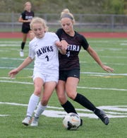 Corning's Ashlee Volpe (1) and Elmira's Katie Schrom fight for possession during the Hawks' 2-1 victory in girls soccer Sept. 12, 2019 at Ernie Davis Academy.