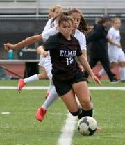 Ireland Krawczyk of Elmira dribbles the ball as Corning's Maddy Gill defends Sept. 12, 2019 at Ernie Davis Academy.