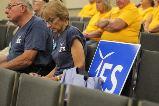 A pair of supporters of the Republic Wind Farm project listened to public testimony Thursday at Tiffin University. The proposed project would put 47 wind turbines in Seneca and Sandusky counties.