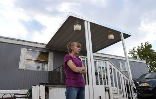 Karla Lyons is pictured outside her mobile home at the Lamplighter Village in Federal Heights on Aug. 30, 2019. Lyons' waitressing wages are eaten up by a constant stream of home and yard repairs ordered by her park manager, including removal of a giant maple tree that fell on her patio roof and crushed it. She would move if she could afford it.