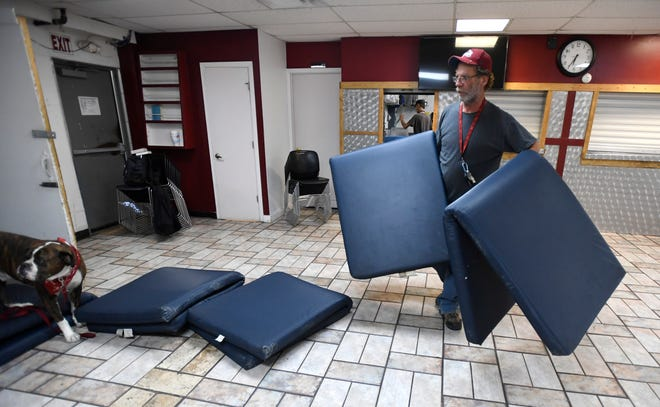 Terry Fritz lays out sleeping mats as the cafeteria becomes a sleeping area after dinner for Terry and the other men staying the night at the Fort Collins Rescue Mission in Fort Collins, Colo. on Sept. 12, 2019.