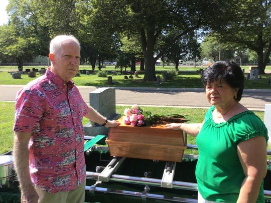 JIm and Gloria Matthews touch the small casket containing their youngest daughter's remains in mid-August. Jonelle was reburied during a service at Linn Grove Cemetery in Greeley.